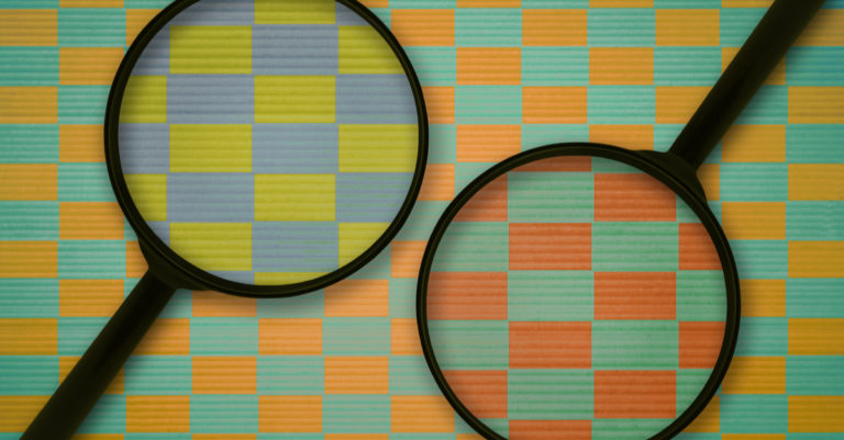 Private versus public sector procurement represented by two magnifying glasses over different color paper