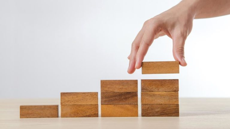Scaling sales represented by increasing stacks of wood blocks