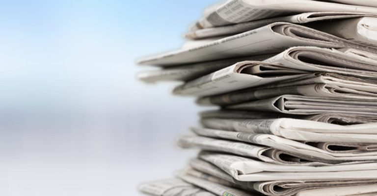 News roundup with a stack of newspapers