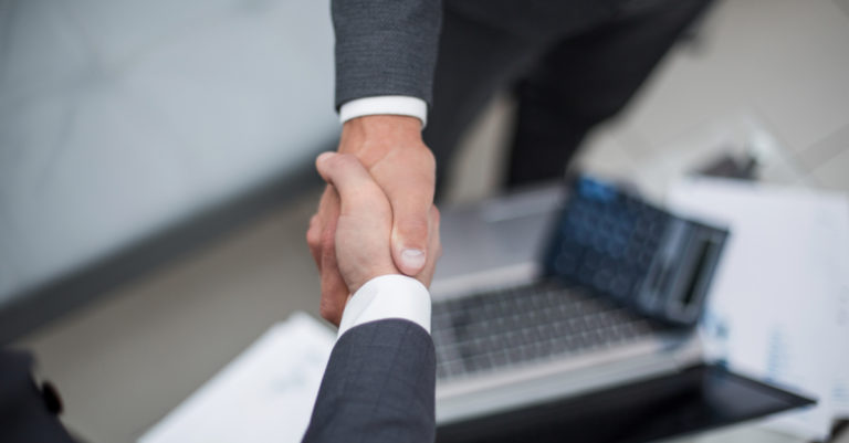7 metrics for company performance represented by business people shaking hands