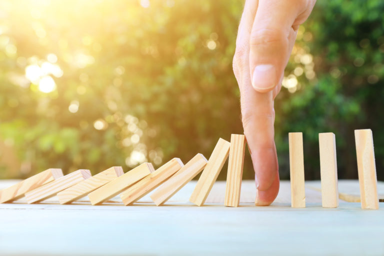 Hand stopping dominoes in context of contract management process and relationship lifecycle